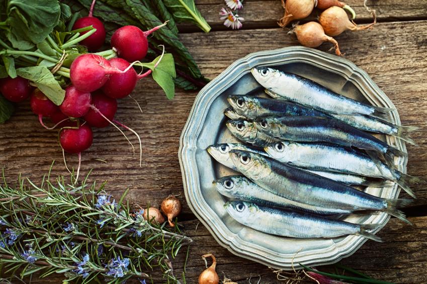 Fresh sardines. Fish with vegetables. Mediterranean fish on plate