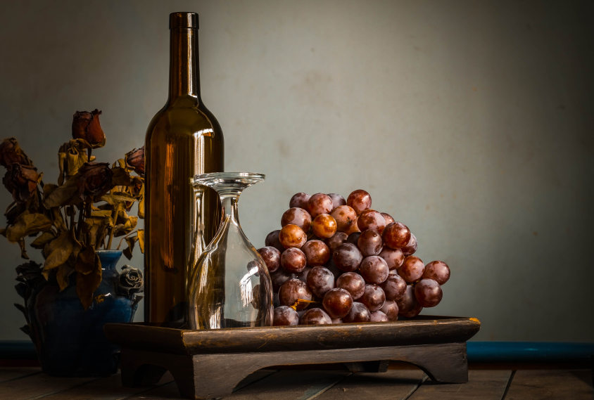 Empty glass and grapes on tray.