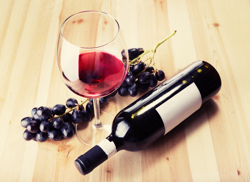 Red wine glass bottle and grapes on wood table