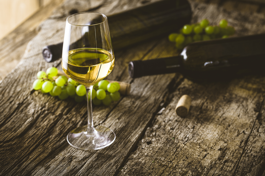 A glass of white wine next to green grapes
