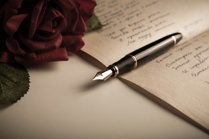 A close up of a fountain pen and rose, laid out on a sheet of paper
