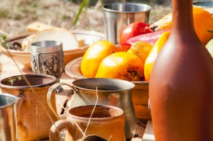 Mug, clay bottle on table laying on the ground in the medieval picnic