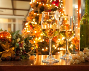 Bottle of Wine and Glasses against Christmas Lights