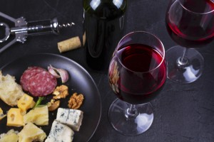 Glass and bottle of red wine, cheese, bread, garlic, nuts, salami on gray stone texture background. View from above