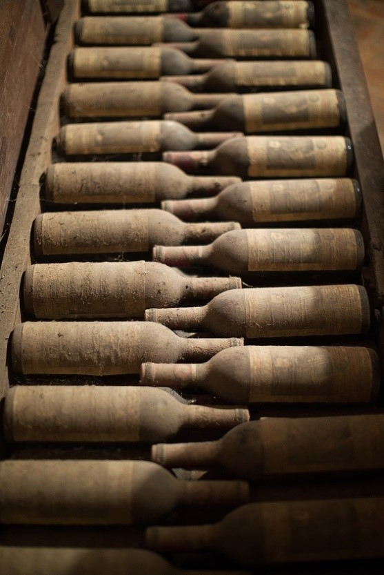 A collection of dusty vintage fine wine stored in a crate