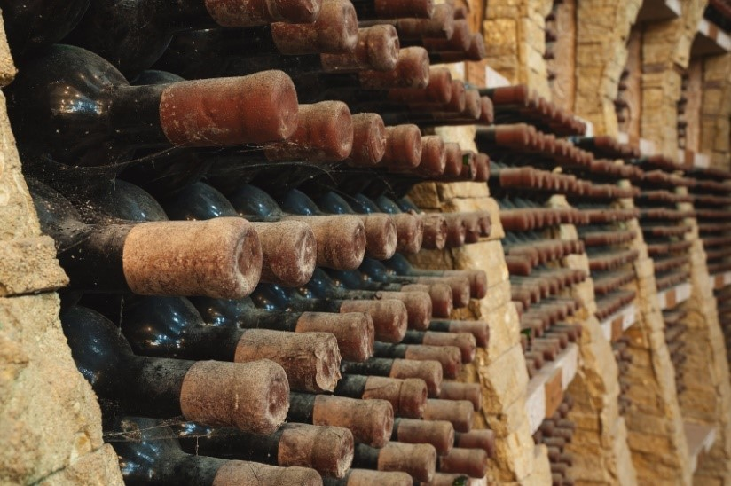 vintage bottles of wine gathering dust in a wine cellar stored in rows