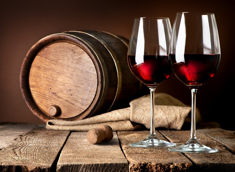 two glasses of red wine next to a wine barrel and a cork