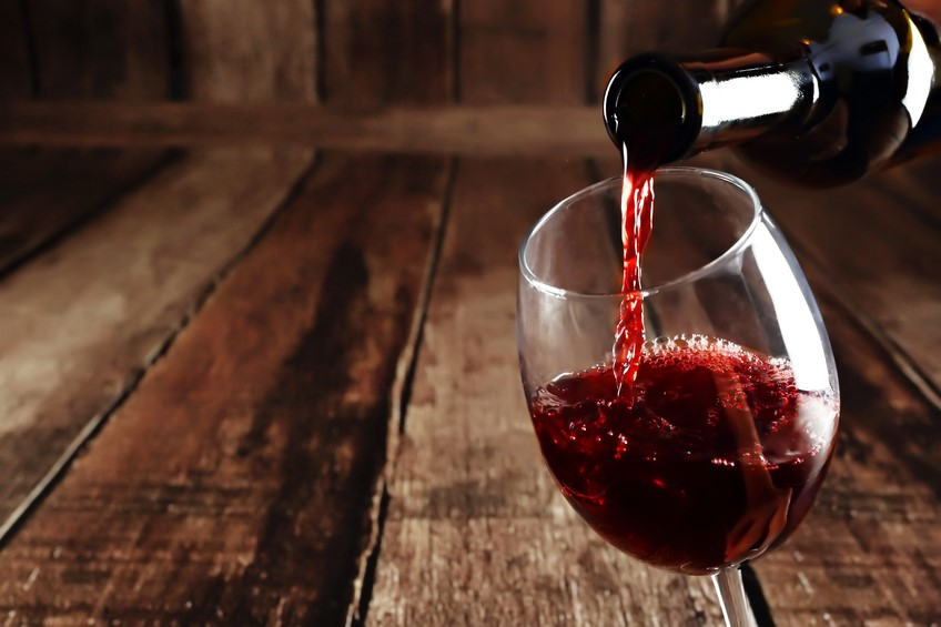 a bottle of red being poured into a glass after being stored in a spiral cellar