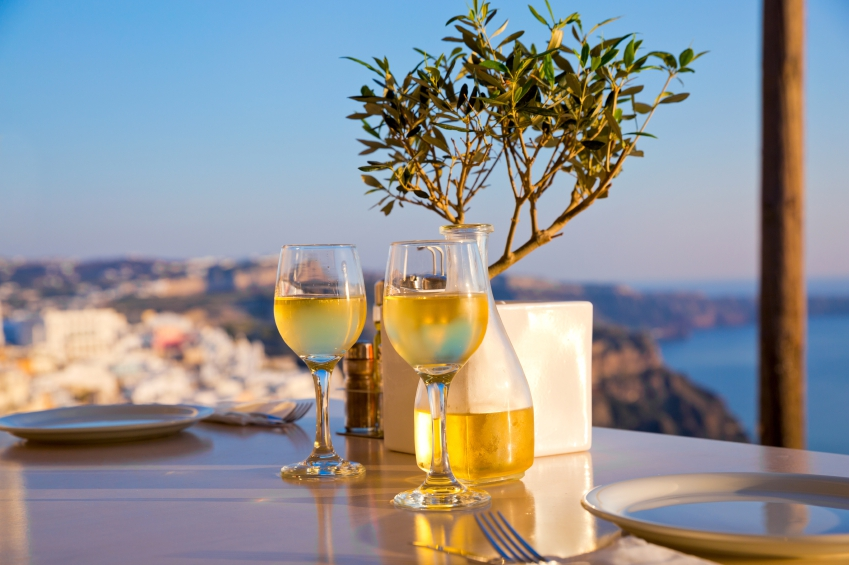 two glasses of white wine against a tropical backdrop on a restaurant table