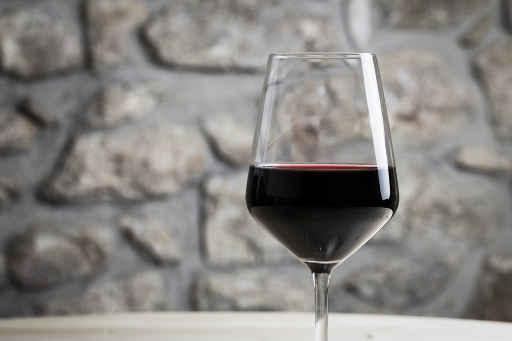 a single glass of red wine after being stored by a spiral cellar